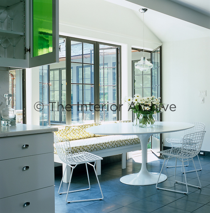 An upholstered bench and Bertoia dining chairs surround a white Saarinen Tulip table in the kitchen/diner