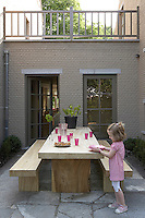 A young girl brings out plates to lay on the rough-hewn garden table and benches which are made of weather-proof wood