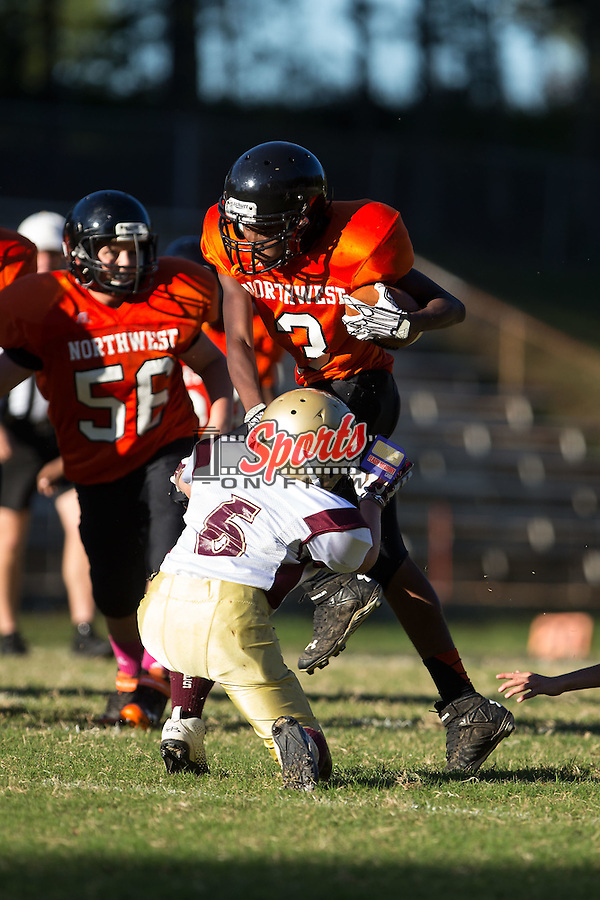Trevon Dozier (3) of the Northwest Cabarrus Titans runs with the football against the Winkler Wolves in 7th grade football action at Trojan Stadium October 7, 2014, in Concord, North Carolina.  The Titans defeated the Wolves 58-30.  (Brian Westerholt/Sports On Film)