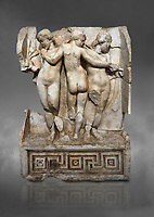 Roman Sebasteion relief  sculpture of the Three Graces, Aphrodisias Museum, Aphrodisias, Turkey.  Against a grey background.<br /> <br /> The Three Graces stand in their familiar hellenistic composition. They were handmaids of Aphrodite and appeared in this form on the decoration of her cult statue at Aphrodisias. Their names evoked their character: Euphrosyne (joy), Aglaia (Splendour) and Thaleia (Bloom).