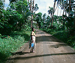 Lady posing for the photographer while walking back to her home along a palm covered avenue. Fiji Islands, circa 1980.