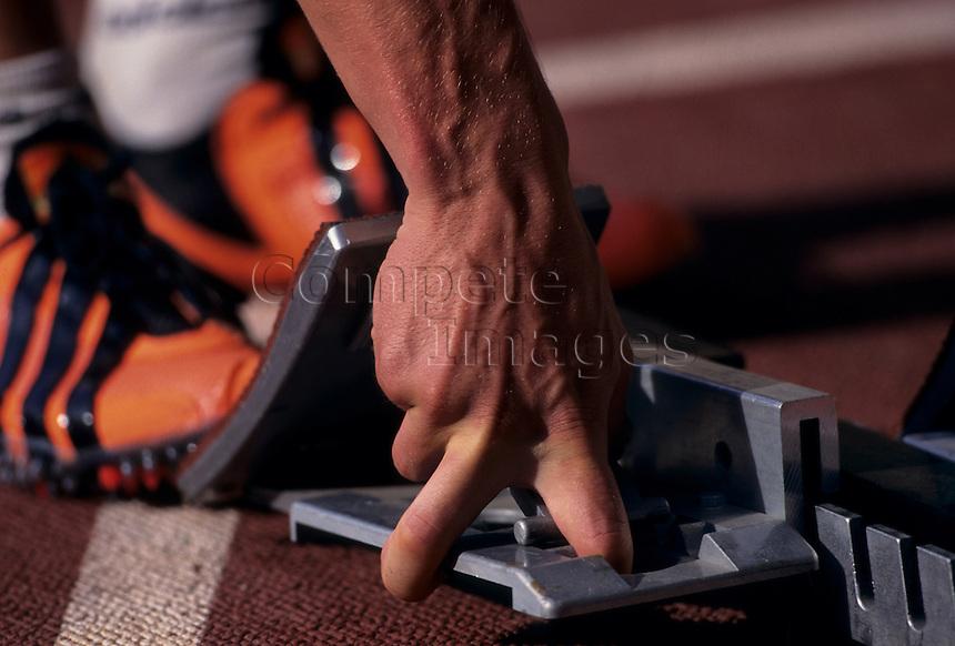 Close up of an athlete adjusting starting block