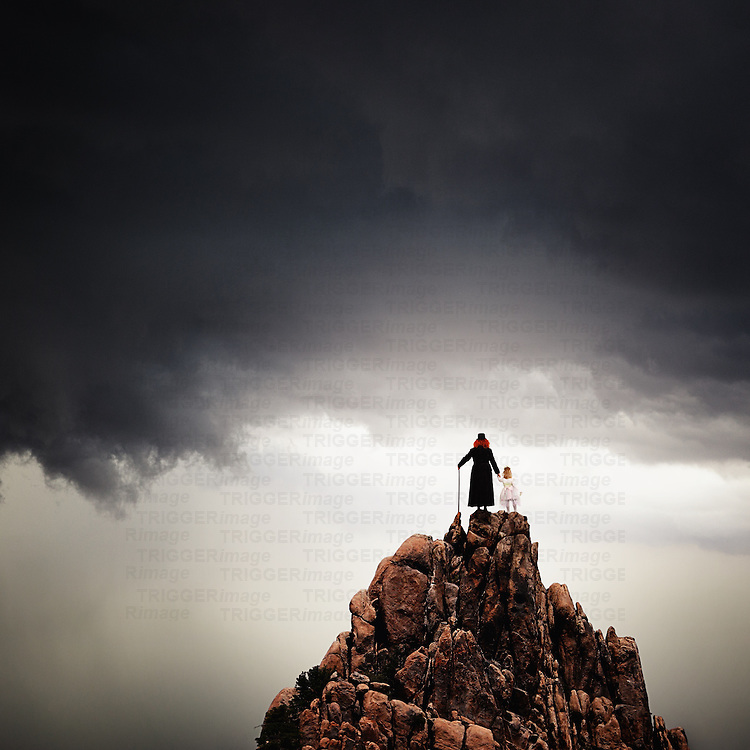 Conceptual image of an adult with red hair wearing a long black coat holding the hand of a young girl wearing a white dress. Both standing on a high rocky hilltop looking into the distance with dark clouds above.