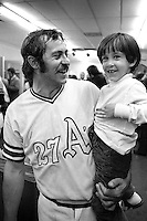 "Oakland Athletics pitcher Jim ""Catfish"" Hunter holding his son Paul in the locker room after the A's had just beaten the Cincinnati Reds in the 1972 World Series.<br />