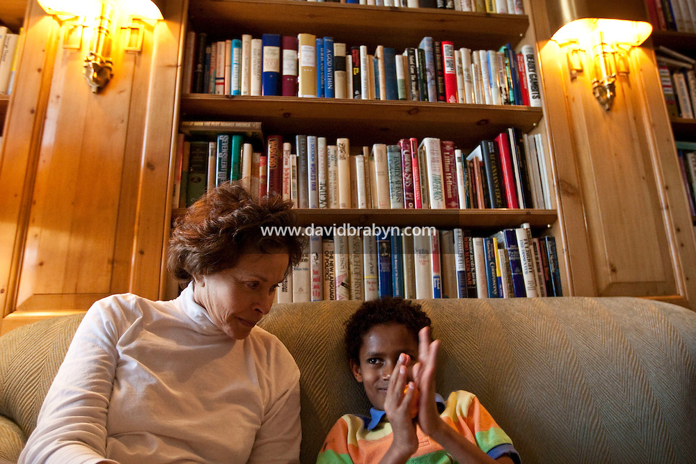 Marilyn Berger (L), widow of Don Hewitt, looks over at Danny Hodes, the 8 year-old Ethiopian boy she has taken in, as he plays with play-doh in her apartment in New York, NY, USA, 9 April 2010. Ms Berger met him in Addis Ababa while reporting there and helped him get surgery.