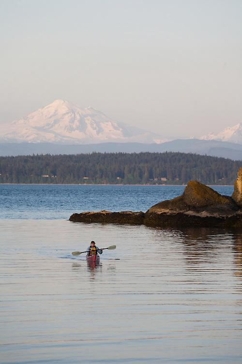 San Juan Islands, Sea kayaker, Mount Baker, Clark Island Marine State Park, Salish Sea, Washington State, Pacific Northwest, U.S.A., woman paddler, released,.