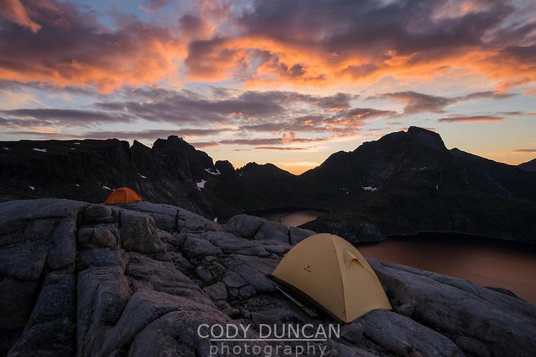 Tents pitched on rocky terrain near summit of Moldtind mountain peak, Moskenesøy, Lofoten Islands, Norway