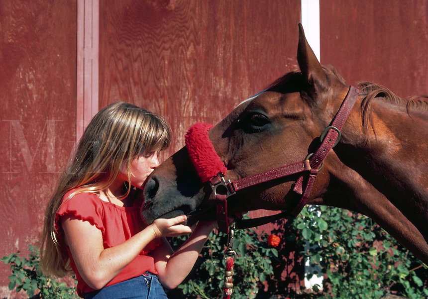 Young girl kissing her horse at Laguna Beach, California