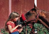 Young girl kissing her horse at Laguna Beach, California