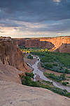 Viewed from Tsegi Overlook, a passing summer monsoon storm leaves the typically dy Chinle Wash flooded from heavy rains