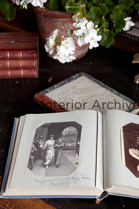 """A family photograph album (from the Collis-Sandes family) sits across a handwritten journal with the """"Standing Orders for the Movable Column of the Peshawur Force,"""" a relic of the days of the Raj"""