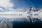 Norway, Svalbard, open fjord in late spring, mountains and clouds reflected in calm water