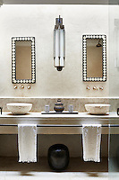 The bathroom is decorated in neutral tones with two stone washbasins set on a shelf unit with mirrors above