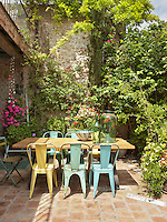 Outdoor dining area on the patio looking towards stone wall with bougainvillea