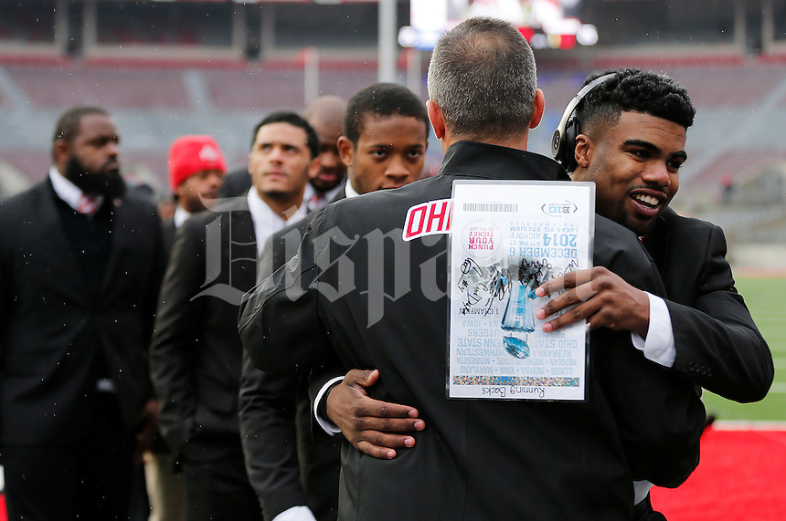 Ohio State Buckeyes running back Ezekiel Elliott (15) hugs head coach Urban Meyer as the team walks on to the field before the college football game between the Ohio State Buckeyes and the Indiana Hoosiers at Ohio Stadium in Columbus, Saturday morning, November 22, 2014. (The Columbus Dispatch / Eamon Queeney)