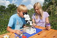 Kind, Kinder mit Binokular im Garten, Stereolupe, Lupe, betrachten Federn und Pflanzendetails