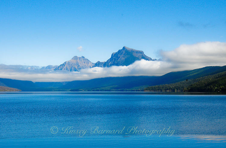 White, billowy clouds hang over Lake McDonald in Glacier National Park Montana