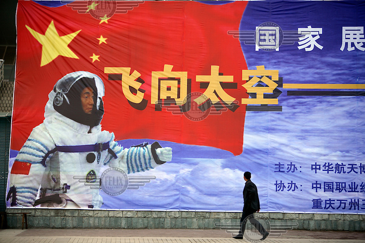 A pedestrian walks past a large picture of a Chinese astronaut (taikonaut). China launched it's Chang'e 1 moon orbiter in November 2007.