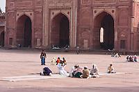 Fatehpur Sikri, Uttar Pradesh, India.  Men Sitting in Courtyard of Jama Masjid (Dargah Mosque).  Buland Darwaza (Great Gate) in Background.