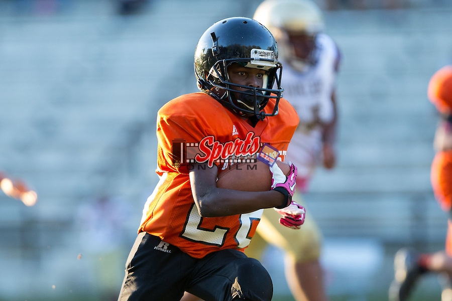 DeAvion Pless (28) of the Northwest Cabarrus Titans runs with the football against the Winkler Wolves in 7th grade football action at Trojan Stadium October 7, 2014, in Concord, North Carolina.  The Titans defeated the Wolves 58-30.  (Brian Westerholt/Sports On Film)