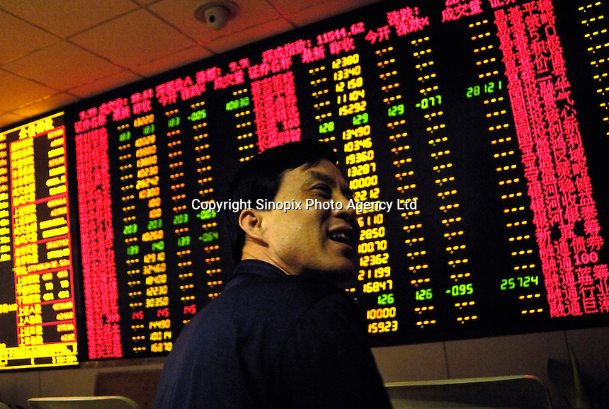 Chinese investors watch stock index in a stock exchange of Beijing. Chinese share prices broke through the psychologically important 4000-mark for the first time ever yesterday and dealers said the sustained Chinese advance is being driven by massive inflows of fresh funds as smaller investors take their money out of low-return bank deposits and punt on stocks..10 May 2007