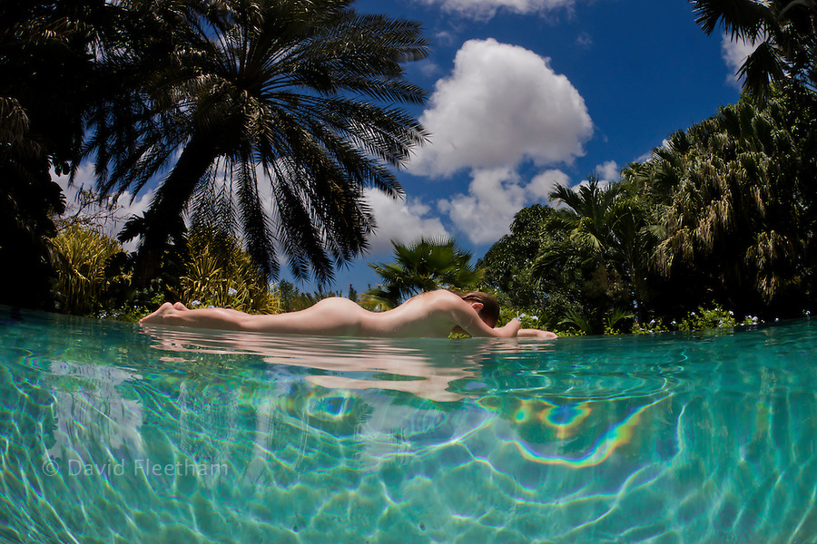 A woman lies naked at the edge of an infinity pool with a tropical background on the island of Curacao, Netherlands Antilles, in the Caribbean.