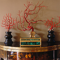 The English demi-lune console table dates from George III and displays a gilded malachite box and a collection of coral and branches painted to match