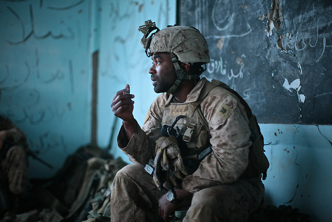 With his wrist still covered in blood, Navy corpsman Jonathan Duhart smokes a cigarette after Lance Cpl. Matthew W. McElhinney, of Company L, 3rd Battalion, 6th Marine Regiment is picked up by a medevac helicopter near Marjah, Afghanistan. The Marines later receive word that McElhinney's pelvis was shattered by the bullet that struck him, but that he will survive. March 10, 2010. DREW BROWN/STARS AND STRIPES