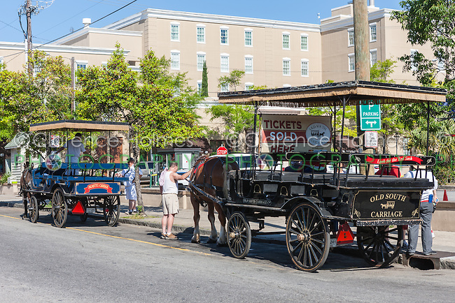 Horse-drawn carriage tour operators sell tickets and prepare for the next trip on N Market Street in Charleston, South Carolina.