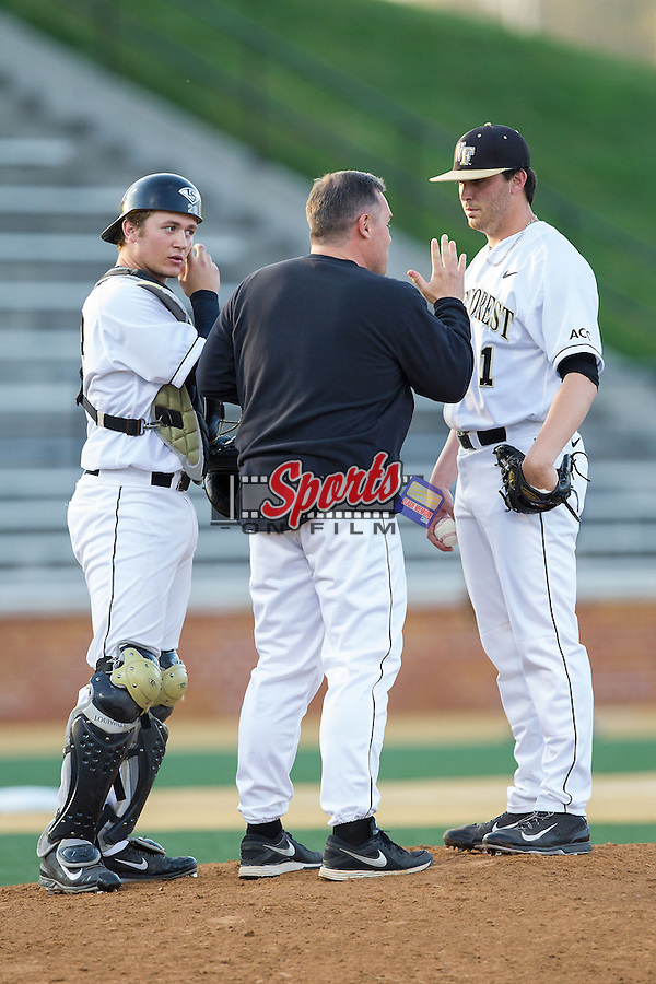 Wake Forest Demon Deacons starting pitcher Matt Pirro (1) and catcher Garrett Kelly (28) listen to pitching coach Dennis Healy (31) during the game against the High Point Panthers at Wake Forest Baseball Park on April 2, 2014 in Winston-Salem, North Carolina.  The Demon Deacons defeated the Panthers 10-6.  (Brian Westerholt/Sports On Film)