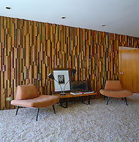 One wall of this retro-style living room is covered in a textured wood panelling contrasting with the shag-pile carpet on the floor