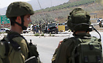 Israeli soldiers gather next to a vehicle belonging to a Palestinian man after he reportedly charged it into a group of soldiers at the Israeli army Hawara checkpoint near the city of Nablus in the occupied West Bank on July 31, 2016. A Palestinian armed with a knife charged at Israeli soldiers on the outskirts of the city of Nablus in the occupied West Bank and was shot dead, the Israeli army said. The Palestinian health ministry identified the person killed as Rami Awartani, 31. Photo by Nedal Eshtayah
