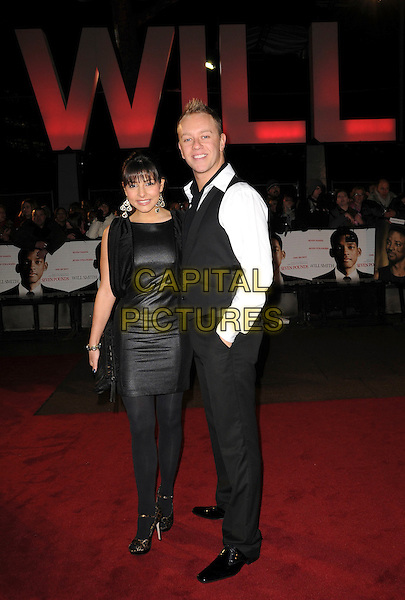 """ROXANNE PALLETT & GUEST .Attending the UK Film Premiere of """"Seven Pounds"""" at the Empire Cinema, Leicester Square, London, England, January 14th 2009..full length black dress shiny tights leopard print shoes peep toe mary janes waistcoat white shirt .CAP/CAS.©Bob Cass/Capital Pictures"""
