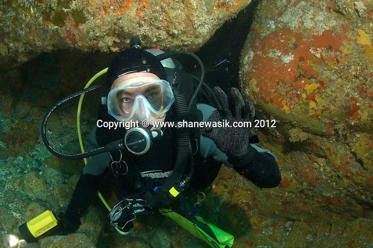 Around 36m underneath the cave at Astrolave Reef is a small swim through. The diver has exited onto the open reef side. This image was taken prior to the MV Rena wrecking in 2011.