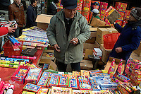 A fireworks seller looks over his wares at a Lunar New Year market in Pukou near Nanjing, Jiangsu, China.  Lunar New Year is also known as Chinese New Year.  2009 is the Year of the Ox, or Year of the Cow, or Year of the Bull.