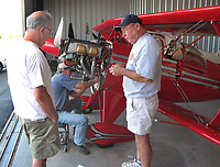 Pilot and aiframe and powerplant mechanic Roger Willis with two pilots as aerobatic Pitts is modified in a hangar at the Petaluma Municipal Airport, Petaluma, Sonoma County, California.