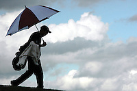 Under stormy skies, a Rocklin golfer walks with an umbrella to the next hole at Morgan Creek Country Club and Golf Course during a golf match against Woodcreek in Roseville, Thursday, April 7, 2005. (Pico van Houtryve/The Press-Tribune)