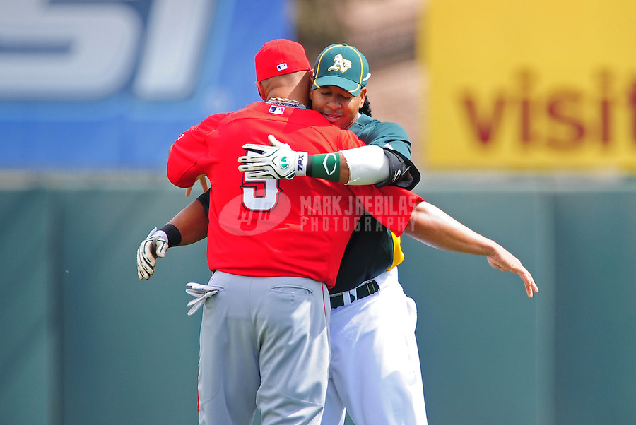 Mar. 4, 2012; Phoenix, AZ, USA; Los Angeles Angels first baseman Albert Pujols (left) greets Oakland Athletics designated hitter Manny Ramirez prior to a spring training game at Phoenix Municipal Stadium.  Mandatory Credit: Mark J. Rebilas-