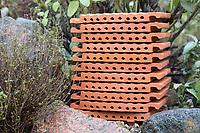 Wildbienen-Nisthilfe aus Strangfalzziegel, Strangfalzziegel, Tonziegel mit Hohlräumen, Biberschwanz, Dachziegel. Stapel, gestapelt in Kräuterbeet. Wildbienen-Nisthilfen, Wildbienen-Nisthilfe selbermachen, selber machen, Wildbienenhotel, Insektenhotel, Wildbienen-Hotel, Insekten-Hotel