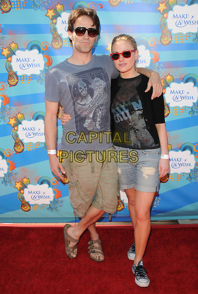 STEPHEN MOYER & ANNA PAQUIN .at the Make-a-Wish Foundation Funday at The Santa Monica Pier in Santa Monica, California, USA, .March 14th, 2010                                                                    .full length sunglasses  black aviators red wayfarers ray bans denim shorts trainers couple black grey gray top t-shirt green khaki sandals converse birkenstock arms around .CAP/RKE/DVS.©DVS/RockinExposures/Capital Pictures