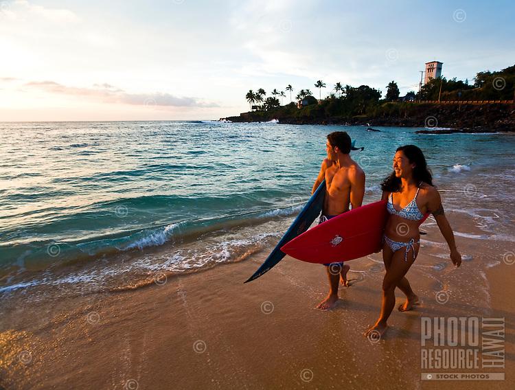 Surfer couple at sunset, Waimea Bay Beach Park, North Shore of Oahu, Hawaii