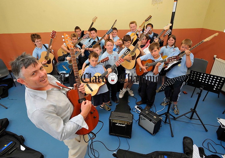 Michael Varden of the Ennis Guitar school with pupils of Barefield NS, who have compeleted preliminary grade in guitar tuition as part of a new graded primary schools initiative by The Ennis Guitar School. Photograph by John Kelly.