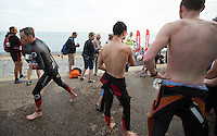 27 JUL 2013 - CROMER, GBR - Benjamin Bailey (left) runs past swim only competitors on his way to transition during The Anglian Triathlon at Cromer, North Norfolk, Great Britain (PHOTO COPYRIGHT © 2013 NIGEL FARROW, ALL RIGHTS RESERVED)