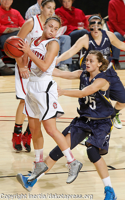 RAPID CITY, S.D. -- DECEMBER 7, 2013 -- Tia Hemiller #4 of the University of South Dakota grabs a rebound in front of Devyn Asche #25 of South Dakota Mines during their game Saturday at the Rushmore Plaza Civic Center Ice arena in Rapid City, S.D.  (Photo by Dick Carlson/Inertia)