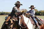 A cowboy father on horseback showing his son how to throw a rope to catch cattle roping lasso