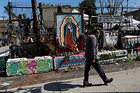 NEW YORK, NY - April 14: A man wearing a face mask crosses the altar of the Virgin of Guadalupe on April 14, 2020 in Brooklyn, NY. The global number of deaths from COVID-19 has reached 122,000 and infected more than 1.9 million people. Experts believe the number may be greater. (Photo by Pablo Monsalve / VIEWpress via Getty Images)
