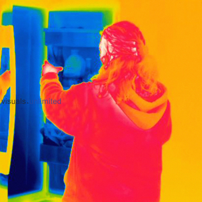 Thermogram of an adult woman getting item from the refrigerator. The temperature scale runs from white (warmest) through red, yellow, green and cyan, blue and black (coldest).