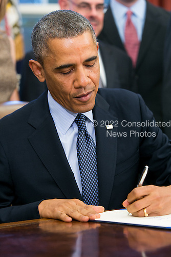 United States President Barack Obama signs the School Access to Emergency Epinephrine Act (H.R. 2094) in the Oval Office of the White House on November 13, 2013 in Washington, DC. <br /> Credit: Kristoffer Tripplaar  / Pool via CNP