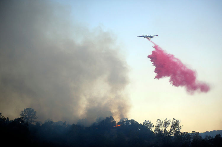 Winters, California, U.S. - Fire fighting air craft made fire retardant drops in an attempt to slow the growth of the Quail Fire in Solano County Saturday. The fire was moving fast and was burning past the retardant lines the tankers were dropping.