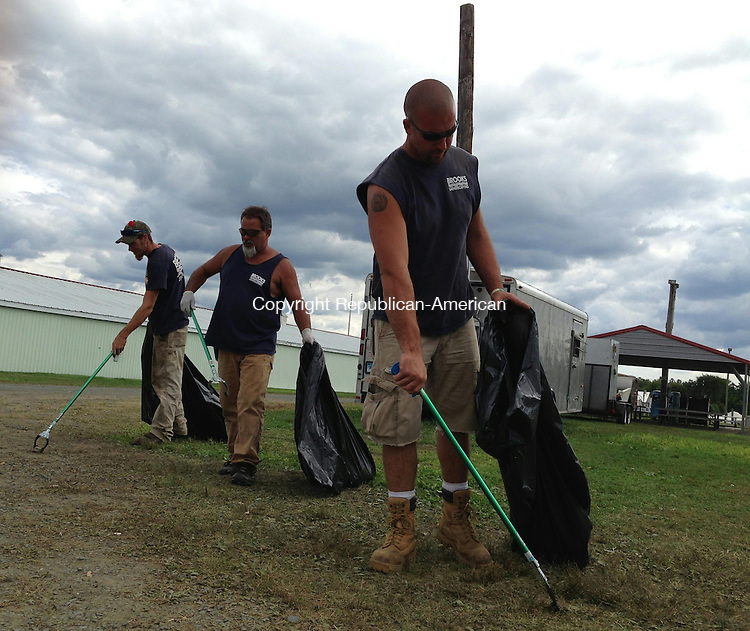 BETHLEHEM, CT - 8 Sept 2014 - 090814RH01 - Larry Dubey, right, Chris Saren, center, and J.J. Stuart of Brooks Landscapers finish cleaning the grounds the day after the Bethlehem Fair closed. Rick Harrison Republican-American